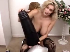 Horny mature woman sits on a giant black sex toy