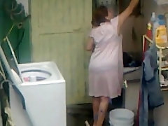 Voyeur shot of a curvaceous mom in the laundry room